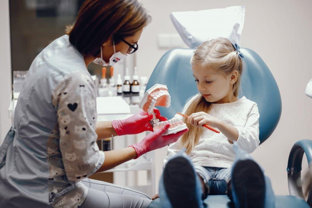 odontoiatria infantile - bambina parla con pedodonzista in studio medico