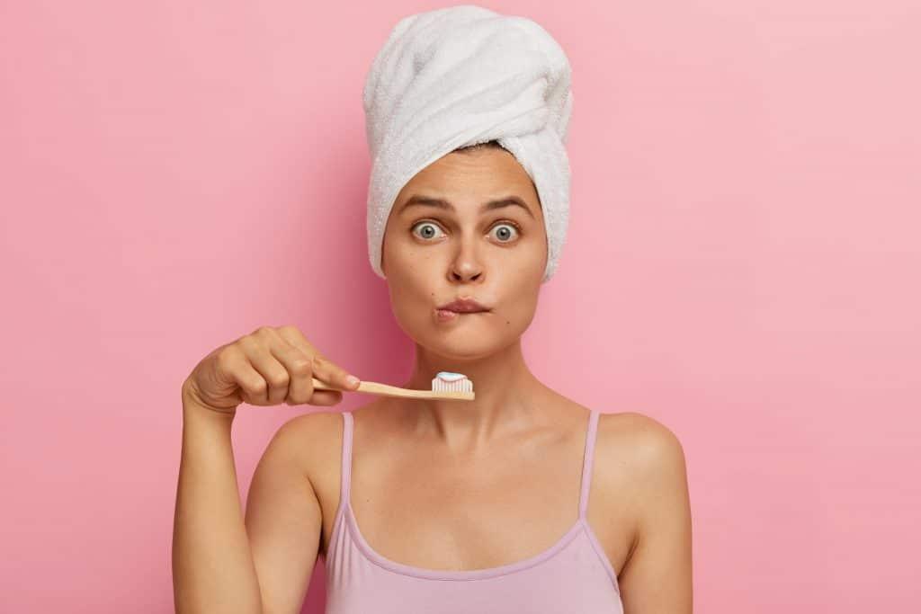Donna che si lava i denti ma non apre bocca perchè ha i denti macchiati