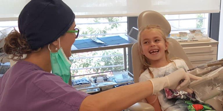 bambina sorridente in studio di odontoiatria infantile