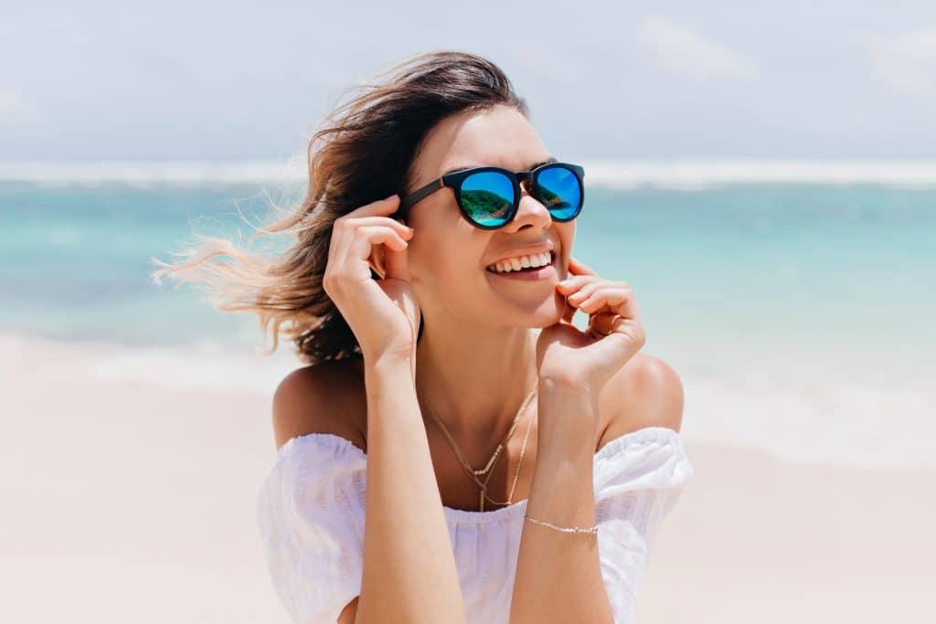 Donna al mare che sorride - proteggere i denti in estate