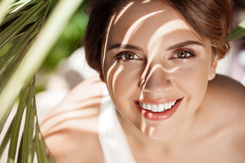 donna sotto un albero ch sorride e mostra la corretta igiene orale dei suoi denti