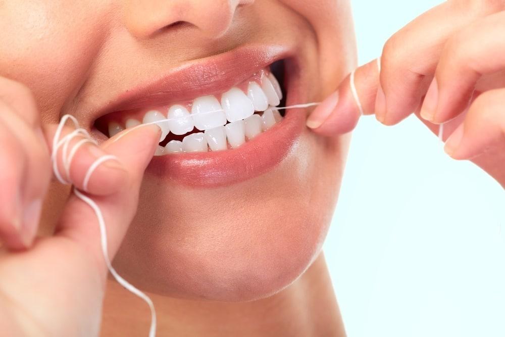 donna che utilizza filo interdentale per corretta igiene orale