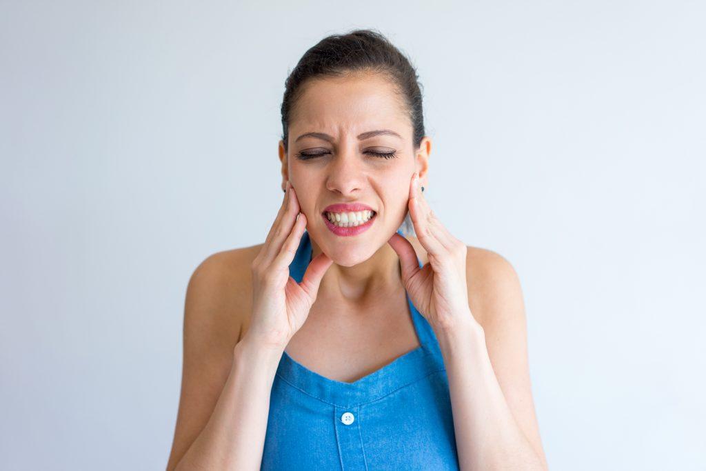 donna dolorante che si tocca i lati della mandibola causa blocco della mandibola