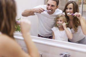 Famiglia che si lava i denti di fronte a uno specchio per combattere sanguinamento gengivale