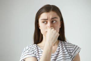 Donna che si tappa il naso per alitosi rimedi