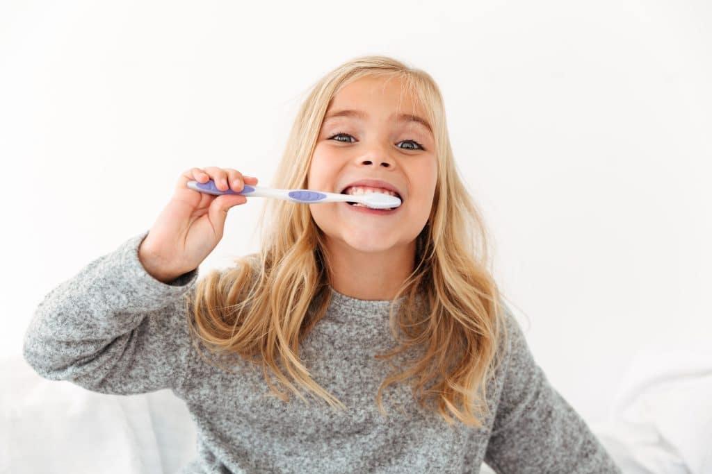 bambina che si pulisce bene i denti dopo aver avuto stomatite nei bambini