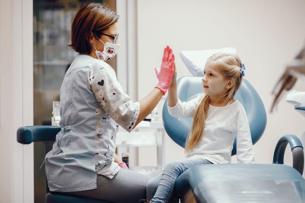 bambina batte il cinque della pedodonzista per scacciare la paura del dentista