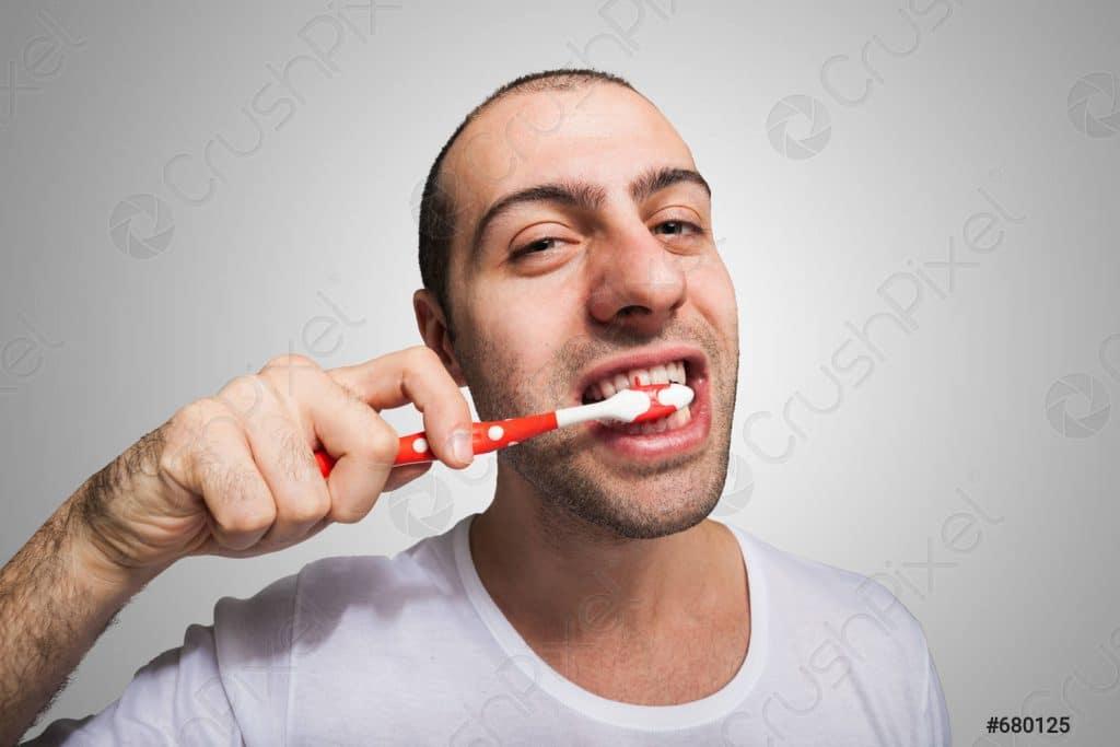 uomo che si lava i denti dopo intervento di chirurgia orale