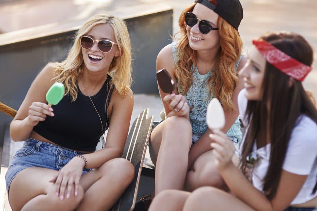 Donne in estate che mangiano gelato e ghiaccioli per non proteggere i denti