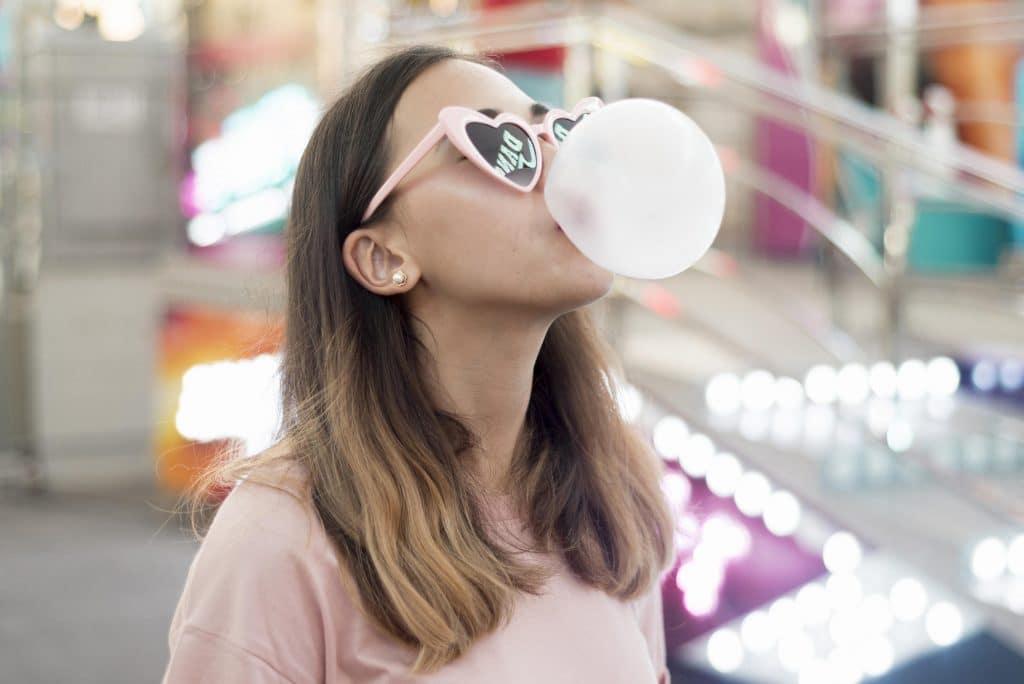 Donna che fa bolla con gomma da masticare . la mastica per proteggere i denti in estate